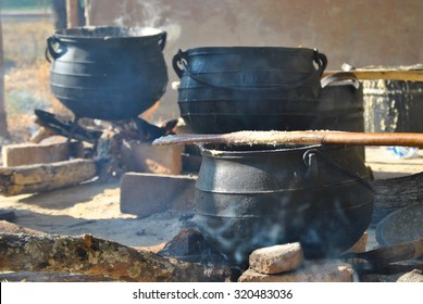 three large cooking pots on fires with smoke