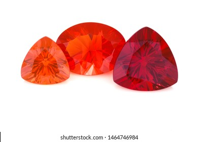 Three large faceted mexican fire opal shown on a white background. The gemstones are of various shape and size and range in shades of orange and red.