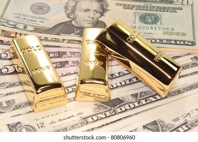 three large gold bars at many dollar bills