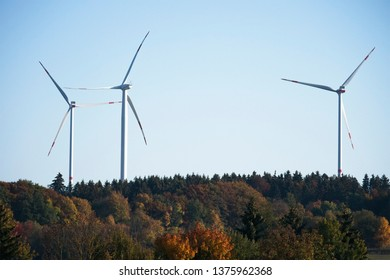 Three large horizontal wind turbines in a forested area