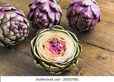 Three large purple fresh artichoke and a half on wooden background