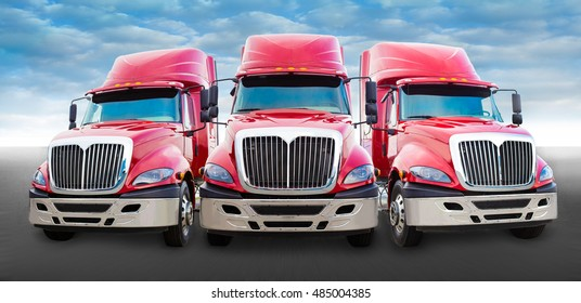 Three large red truck on the road