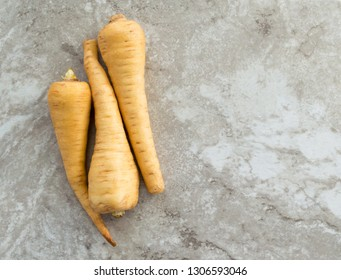 three large ripe parsnips on a gray marble kitchen counter with copy space