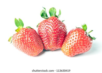 three large ripe strawberries are on a white background