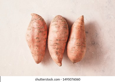 Three large sweet potatoes on a textured pink background, top view.