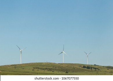 three large wind turbines on a hill producing power for the electricity grid on a sunny day