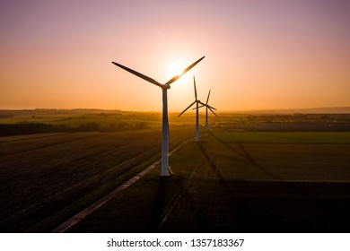 Three large wind turbines at sunrise taken from the air