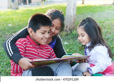 Three latin children reading a book in the park
