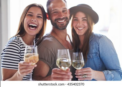 Three laughing friends in front of bright window light holding wine in glasses while celebrating something