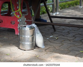 A three layer metal tiffin carrier contains food for someone put on the floor, with rice in plastic bag beside.