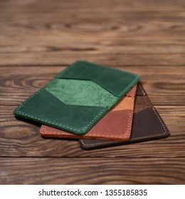 Three leather cardholders lies one another one on wooden background. Green, ginger and brown cardholders on photo. Stock photo with blurred background.