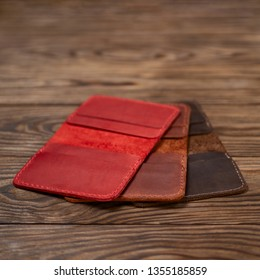 Three leather cardholders lies one another one on wooden background. Red, ginger and brown cardholders on photo. Stock photo with blurred background.