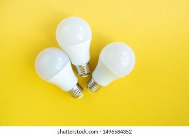 Three LED light bulbs on yellow background. energy saving concept