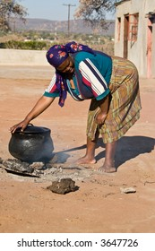 Three legged pot with traditional African food , setswa, African adult woman , people diversity series