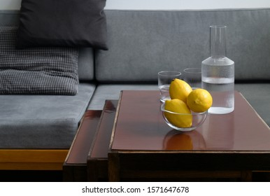 Three lemons in a glass bowl, two glasses and carafe with water on table in empty room, gray sofa with pillows in background