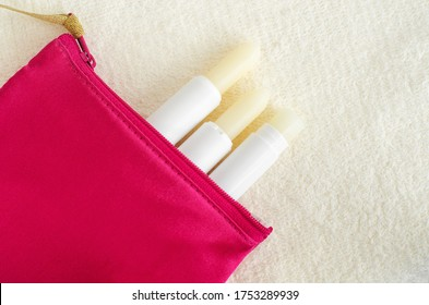 Three lipbalms in the small make-up pouch. Natural lip care concept. Top view, flat lay, copy space.