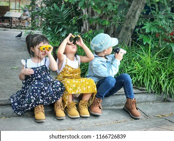 Three little adorable asian kids looking trough a binoculars on sunny summer day in the park. Happy funny children playing outdoors with spyglass in the garden. Travel and adventure concept.