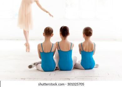 Three little ballerinas with personal ballet teacher in dance studio. classic ballet dancer  as teacher posing on a white background