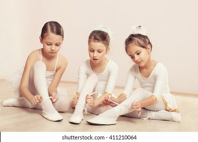 Three little ballerinas sitting on the floor and adjusting their ballet slippers. They are very cute