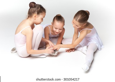 Three little ballet girls sitting in white swimsuit and pointe shoes together with cat on white background in ballet studio