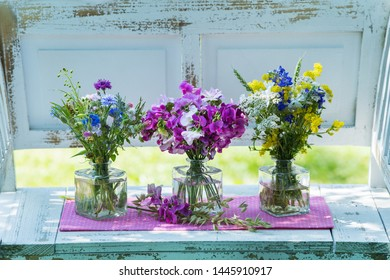 Three little bouquets with wildflowers on a white garden bench