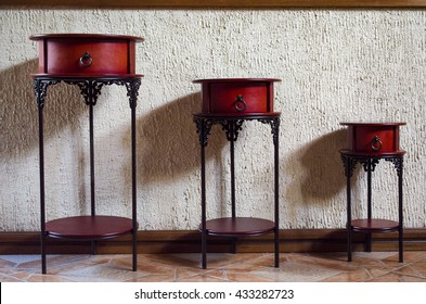 Three little brown tables with drawers lined up by sizes inside a house.