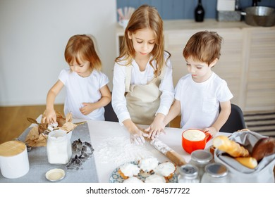 Three little chefs enjoying in the kitchen making big mess. Kids making cookies in the kitchen.