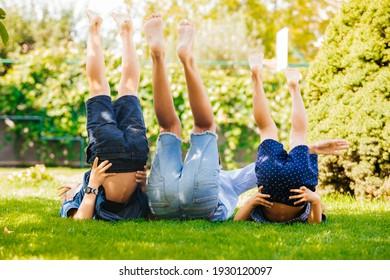 Three little children lying on a green grass