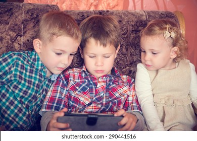 Three little children playing with tablet pc at home