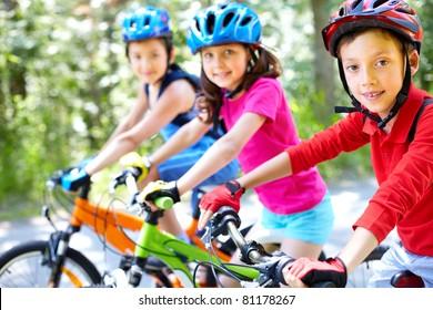 Three little children riding their bikes