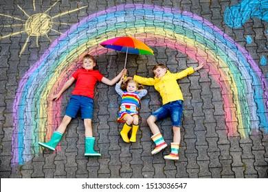 trois petits enfants, deux écoliers et une petite fille s'amusant avec une photo d'arc-en-ciel dessinant avec des craies colorées sur l'asphalte. Frères frères et soeurs en bottes en caoutchouc peignant au sol en jouant ensemble.