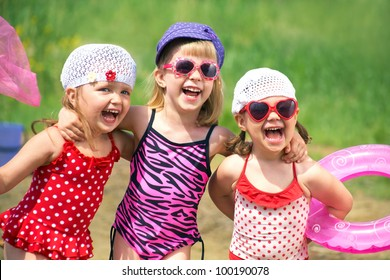 Three little cute girls go swimming in the lake