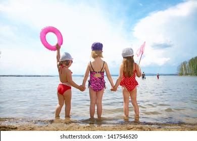 Three little cute girls go swimming in the lake