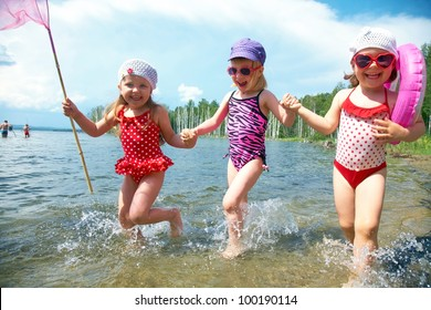 Three little funny  cute girls running on coast together