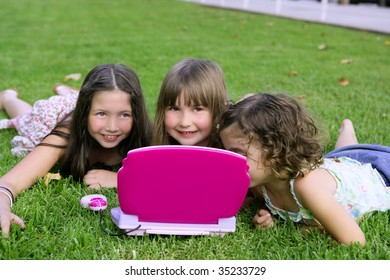 Three little girl outdoor playing with toy computer in grass