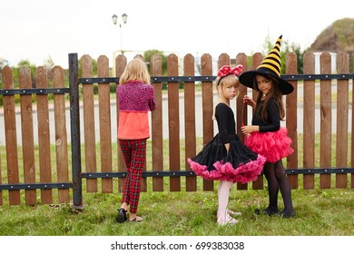 Three little girls in halloween costumes standing by fence in rural environment