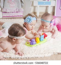 Three little girls playing in the children's room on the carpet near the beds