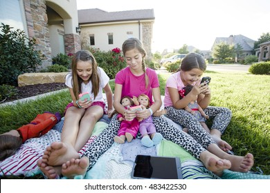 Three little girls playing on their smart phones instead of talking