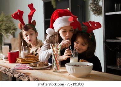 Three little girls of the sister drinking milk and eating cookies in home Christmas holiday. Christmas family portrait.