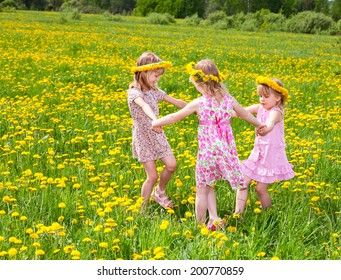 Three little girls wearing dandelion wreath enjoying a summer day outdoors