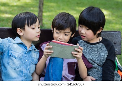 Three Little handsome boy looking on ipad tablet and playing game at park