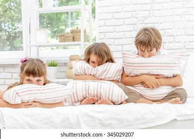 three little happy kids playing on white bed at home