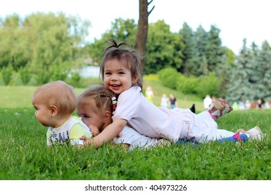 Three little happy smiling friends have a fun on meadows, playing outdoors in spring park, summer and spring outdoors
