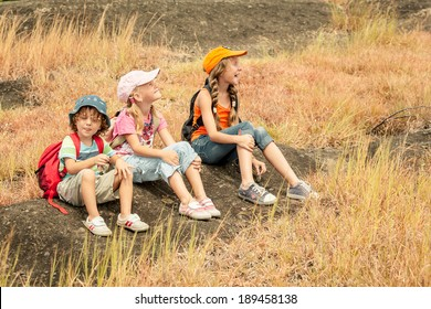 three little kids with backpack sitting on the footpath in the mountains
