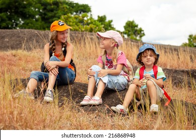 three little kids with backpack sitting on the footpath in the mountains at the day time