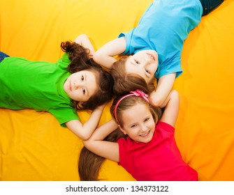Three little kids, boys and girls, laying on the yellow mattress, smiling, with long hair, laying in circle