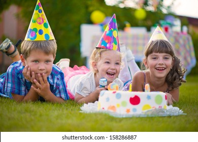 Three little kids celebrating birthday on green grass