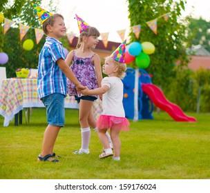 Three little kids celebrating birthday dancing roundelay