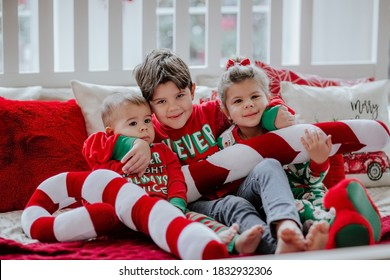Three little kids in Christmas pyjamas laying on white big bed with Christmas pillows.