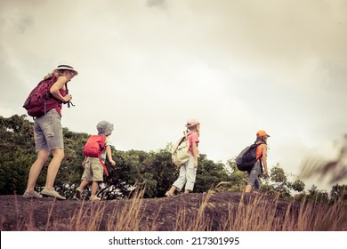 three little kids and mother in the mountains at the day time